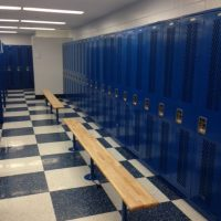 tall blue lockers in locker room with benches