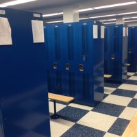 rows of blue lockers and benches in locker room