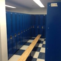 long bench with tall blue lockers in locker room